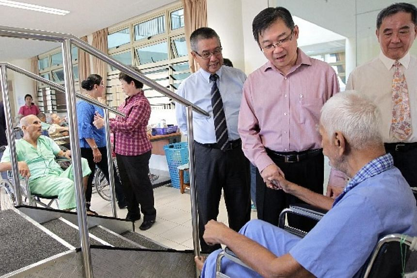 Minister for Health Mr Gan Kim Yong (third from right), accompanied by the president of SAS Mr Eric Teoh (fourth from right), seen at the physiotherapy room during a tour of the Society for Aged Sick's new tower block on July 31, 2014.-- ST PHO