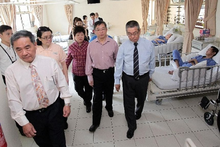 Minister for Health Mr Gan Kim Yong (centre), accompanied by the president of SAS Mr Eric Teoh (right), seen at the wards on the third storey during a tour of the Society for Aged Sick's new tower block on July 31, 2014.-- ST PHOTO: NEO XIAOBIN