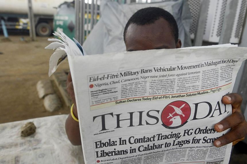 A man reads a newspaper with a headline announcing government efforts to screen for Ebola at a newsstand in Lagos on July 27, 2014.Kenya and Ethiopia, home to some of Africa's largest transport hubs, said on Thursday they had boosted measures t