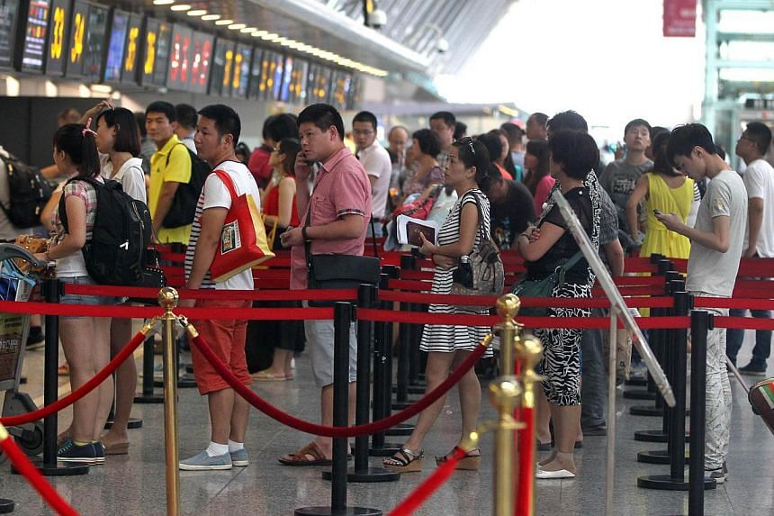 Passengers queue up to check in at Zhengzhou Xinzheng International Airport in Zhengzhou, central China's Henan province on July 29, 2014.China's Defence Ministry on Thursday, July 31 said that military drills in south-east coastal regions were