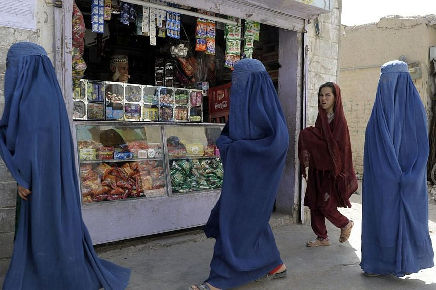 This photograph taken on July 28, 2014, shows Pakistani burqa-clad women as they walk through a market in Quetta in the southwestern Baluchistan province, the site of an acid attack on female pedestrians. -- PHOTO: AFP