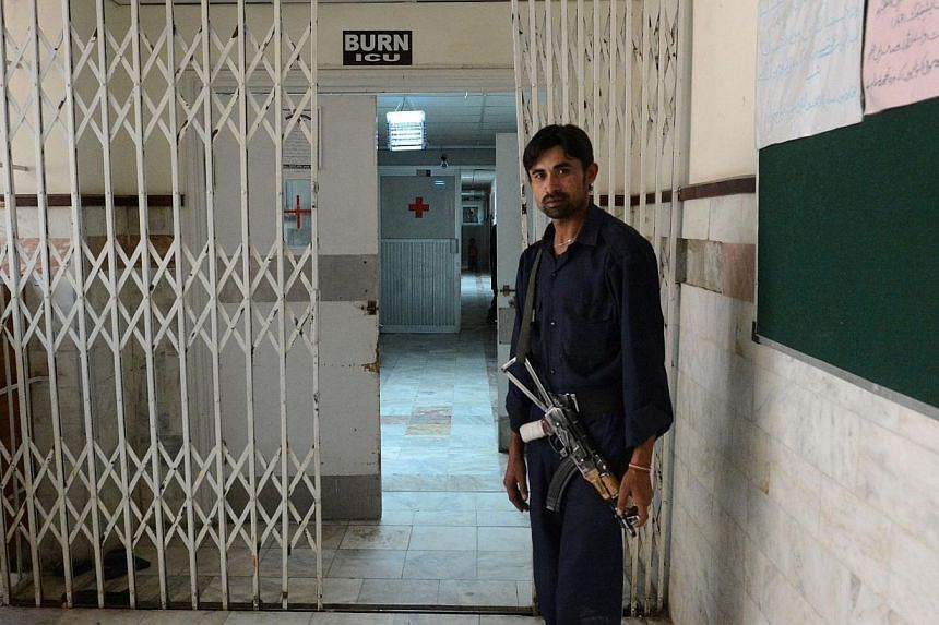 This photograph taken on July 23, 2014, shows a Pakistani security guard standing outside The Burn ICU Department of Bolan Medical Complex in Quetta in southwestern Baluchistan province, where two female acid victims were admitted for treatment. -- P