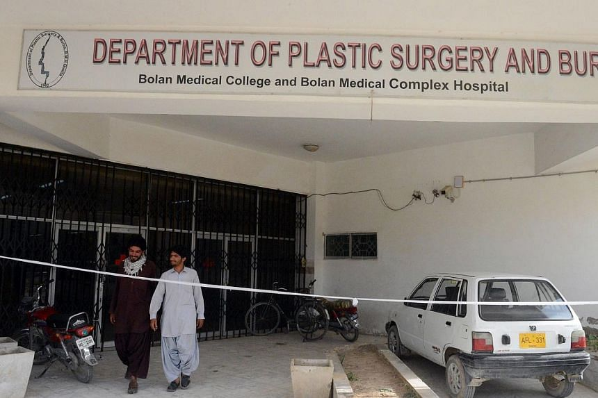This photograph taken on July 23, 2014, shows Pakistani pedestrians as they walk at the entrance of the Department of Plastic Surgery and Burns of Bolan Medical Complex in Quetta in southwestern Baluchistan province, which was cordoned off by the hos