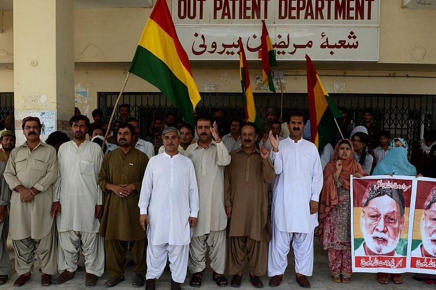 This photograph taken on July 23, 2014, shows Pakistani activists from a regional party of Baluchistan Nationalist Party hold party flags and chant slogans to condemn the recent acid attacks against women outside the Bolan Medical Complex in Quetta i