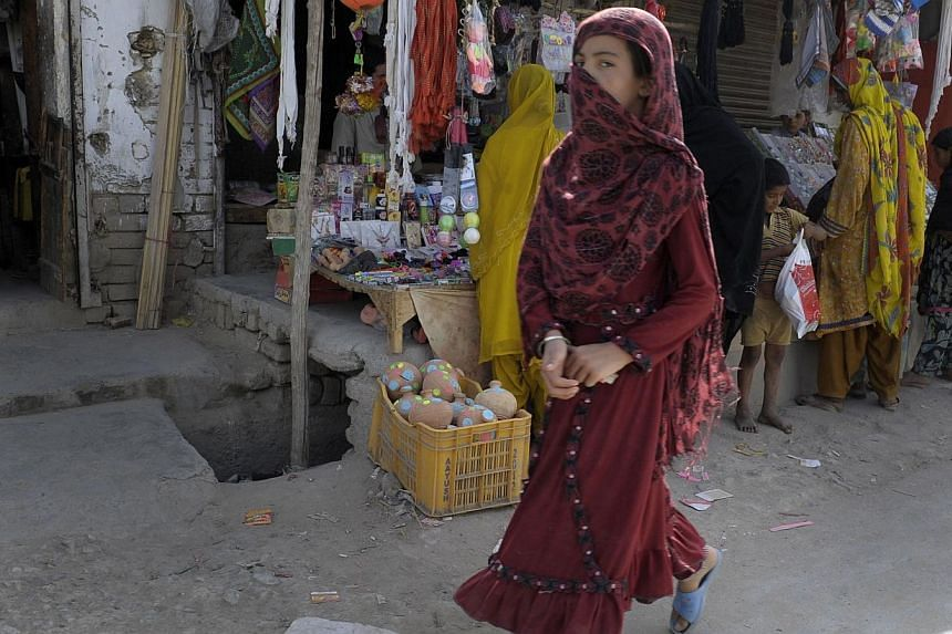 This photograph taken on July 28, 2014, shows a Pakistani female pedestrian as she walks through a market in Quetta in the southwestern Baluchistan province, the site of an acid attack on female pedestrians. -- PHOTO: AFP