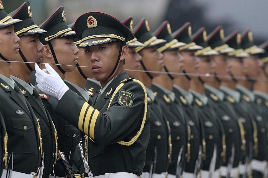 An officer of a Chinese People's Liberation Army honour guard uses a string to ensure members of the honour guard are standing in a straight line, before a welcoming ceremony for Germany's Chancellor Angela Merkel outside the Great Hall of the People