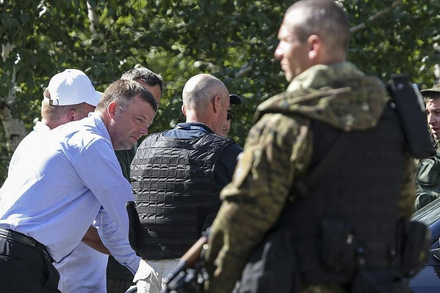 Alexander Hug (left), deputy head for the Organisation for Security and Cooperation in Europe's (OSCE) monitoring mission in Ukraine, looks on next to an armed pro-Russian separatist on the way to the site in eastern Ukraine where the downed Malaysia