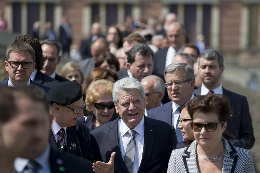 German President Joachim Gauck (centre) and his Polish counterpart Bronislaw Komorowski (3rd right) talk with veterans of the Warsaw Uprising during the opening July 29, 2014, of a Berlin exhibition about the uprising of the Polish resistance against