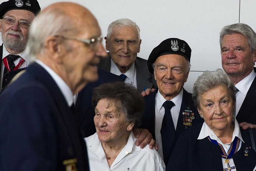 German President Joachim Gauck (background right) poses for pictures with veterans of the Warsaw Uprising during the opening July 29, 2014, of a Berlin exhibition about the uprising of the Polish resistance against Nazi occupiers during World War II.