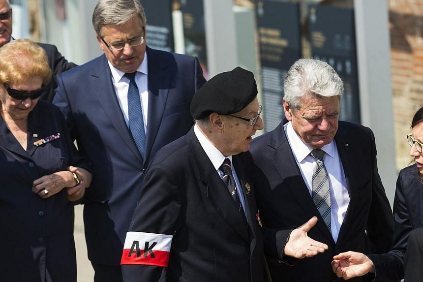 German President Joachim Gauck (2nd right) and his Polish counterpart Bronislaw Komorowski (4th right) talk with veterans of the Warsaw Uprising during the opening July 29, 2014, of a Berlin exhibition about the uprising of the Polish resistance agai