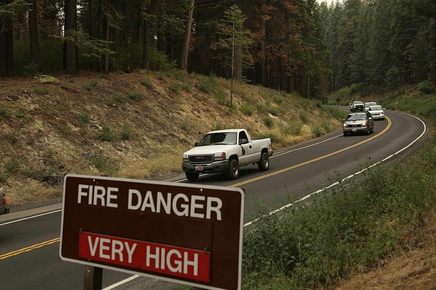 Vehicles are escorted from Yosemite National Park along Highway 120 at the park's entrance in Big Oak Flat, California on July 30, 2014. -- PHOTO: REUTERS