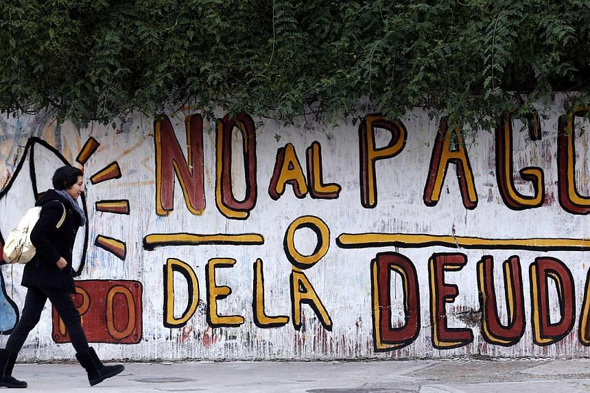 """A woman walks past a graffiti that reads """"No to the debt payment"""" in Buenos Aires on July 28, 2014.Ratings agency Fitch declared Argentina in default on its bonds for the second time in 13 years on Thursday after talks between Buenos Aires and"""