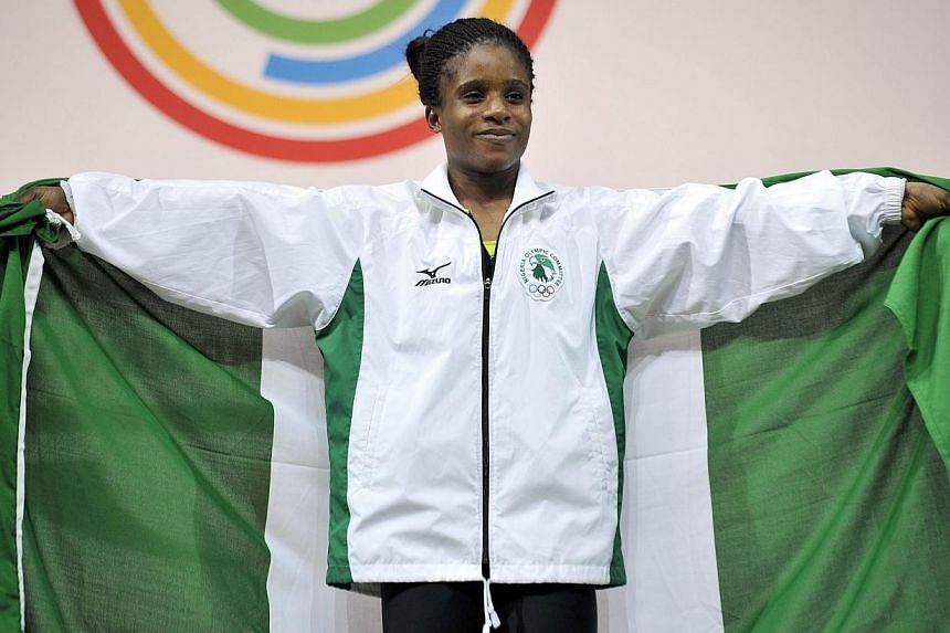 Nigeria's gold medallist Chika Amalaha celebrates on the podium at the medal ceremony for the women's weightlifting 53kg class, at the SECC Precinct during the 2014 Commonwealth Games in Glasgow, Scotland on July 25, 2014.-- PHOTO: AFP