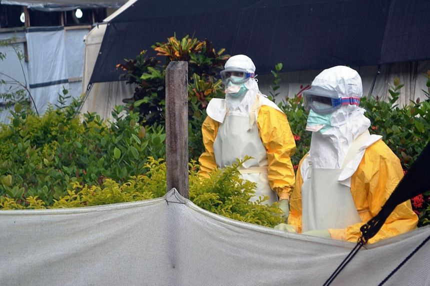 Members of Doctors Without Borders (MSF) wearing protective gear walk outside the isolation ward of the Donka Hospital on July 23, 2014 in Conakry. The World Health Organization warned west Africa's Ebola-hit nations on Friday that the epidemic