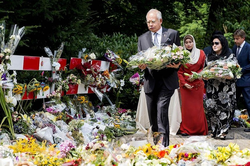 Malaysian Prime Minister Najib Razak and his wife Rosmah Mansor (second, right) lay flowers at the Korporaal van Oudheusdenkazerne in Hilversum, the Netherlands, on July 31, 2014, where the identification process will take place of the victims of the