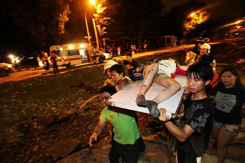 Residents carry a wounded person following a blast in the city of Kaohsiung in southern Taiwan early on Aug 1, 2014. -- PHOTO: AFP