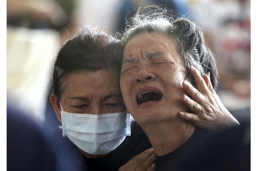 Relatives of the victims cry after an explosion in Kaohsiung, southern Taiwan on Aug 1, 2014. -- PHOTO: REUTERS