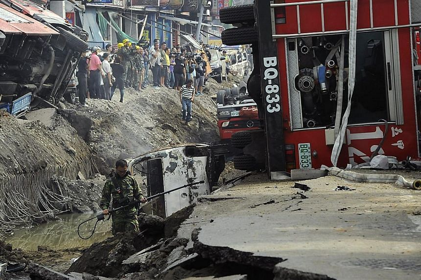 Rescuers survey the wreckage after an explosion in Kaohsiung, southern Taiwan on Aug 1, 2014. -- PHOTO: REUTERS