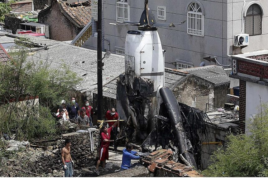 Workers remove the wreckage of a TransAsia Airways turboprop plane that crashed, on Taiwan's offshore island Penghu on July 25, 2014.-- PHOTO: REUTERS