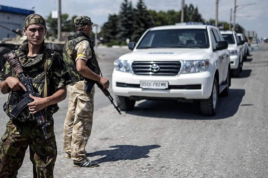 Ukrainian soldiers stand guard on July 31, 2014 near the convoy of the OSCE (the Organisation for Security and Cooperation in Europe) during their mission to reach the crash site of downed Malaysia Airlines flight MH17, at a check-point in the villag
