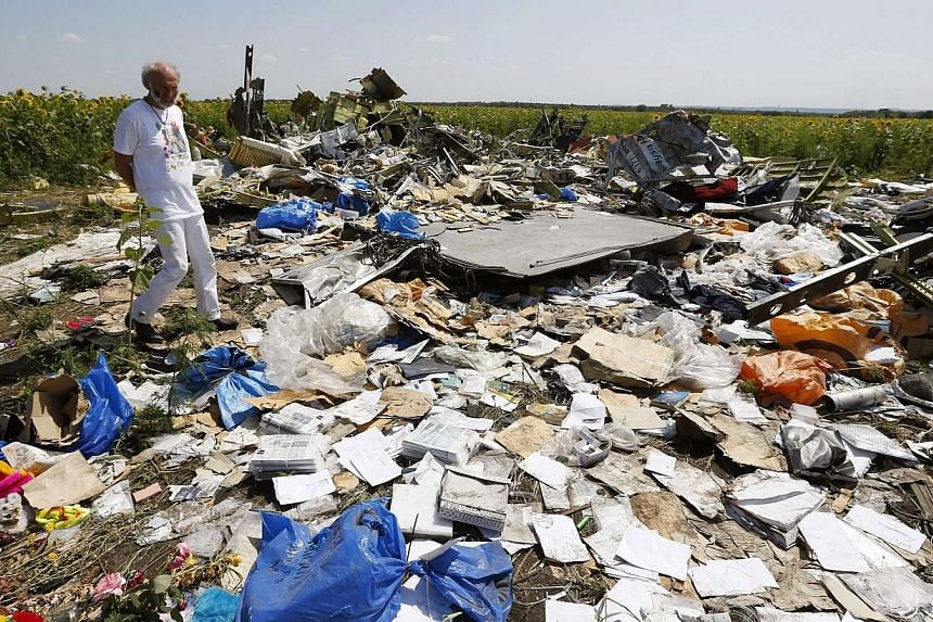 Mr George Dyczynski wears a shirt bearing an image of his daughter Fatima, as he walks through wreckage during his visit to the crash site of the downed Malaysia Airlines Flight MH17, during their visit to the crash site near the village of Hrabove (