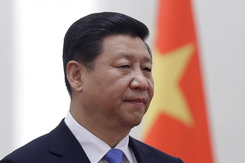 China's President Xi Jinping stands next to a Chinese national flag during a welcoming ceremony at the Great Hall of the People, in Beijing on Nov 13, 2013. -- PHOTO: REUTERS