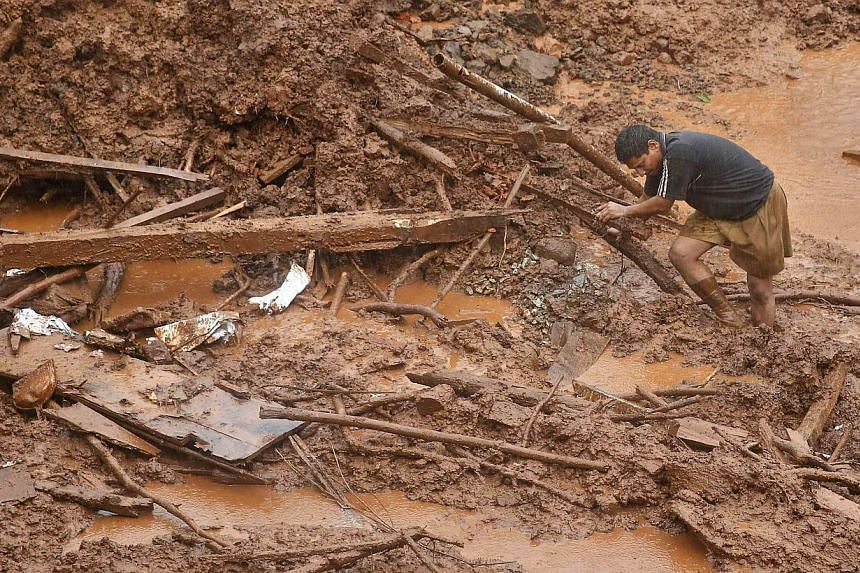 A rescue worker searches for survivors at the site of a landslide at Malin village in the western Indian state of Maharashtra on July 31, 2014. -- PHOTO: REUTERS