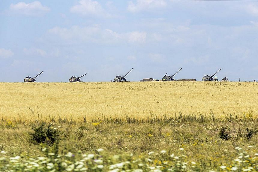 Ukrainian tanks stand guard near a field on July 31, 2014 in the village of Debaltseve, in the Donetsk region, eastern Ukraine.With hazards including blown-up railway bridges and unexploded shells and mines, the route chosen by international in