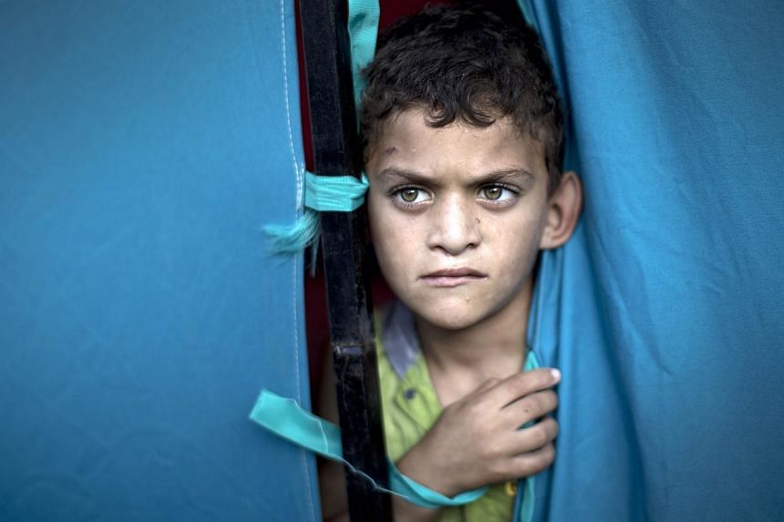 A displaced Palestinian boy looks out from a makeshift tent at the al-Shifa hospital in Gaza City on July 31, 2014. Israel and Hamas have agreed to a 72-hour ceasefire in the Gaza conflict, US Secretary of State John Kerry said early on Friday. -- PH