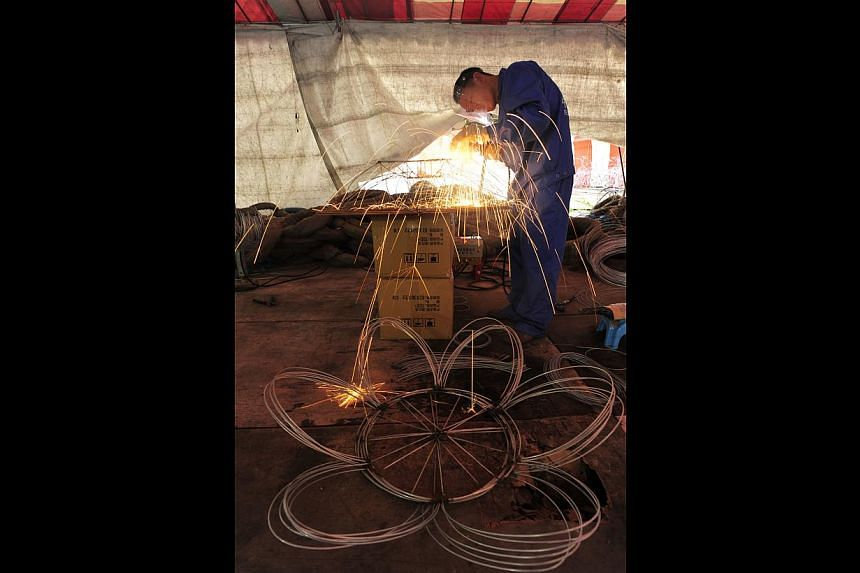 Craftsmen from Sichuan, China, work long hours to complete the flower lanterns, welding raw materials to create a wire frame (above) and leaving the lanterns to air dry after the cloth is glued on (left).