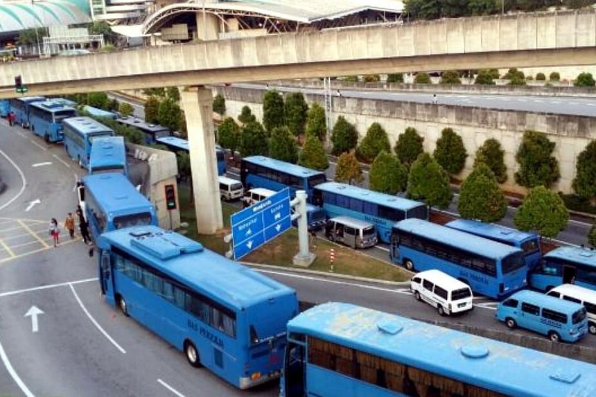 The protest by factory bus drivers at the Bangunan Sultan Iskandar Customs, Immigration and Quarantine (CIQ) Complex, Johor Baru on Friday morning may have been instigated by two drivers, several news portals reported. -- PHOTO: THE STAR/ASIA NE