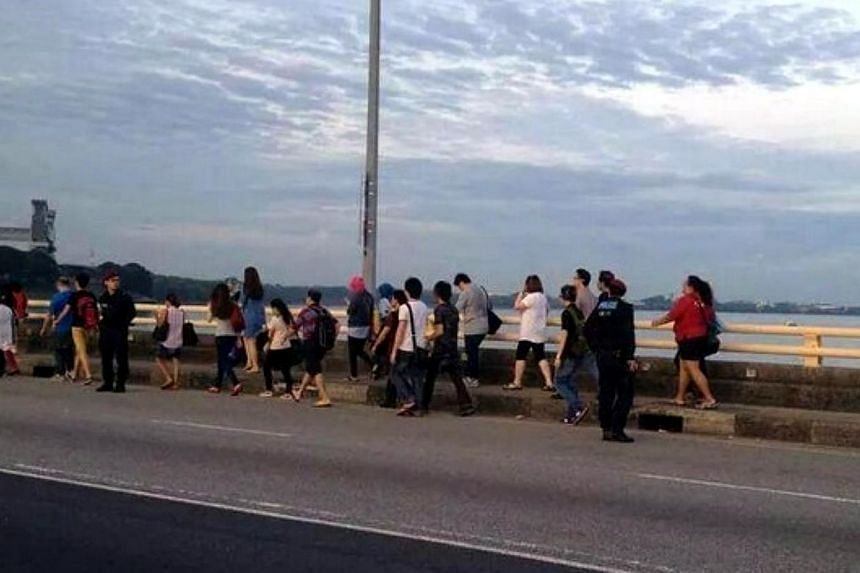 Scores of Malaysian factory workers travelling to Singapore were forced to walk across the Causeway on Friday morning after factory buses refused to cross the checkpoint following the implementation of new toll charges. -- PHOTO: THE STAR/ASIA NEWS N