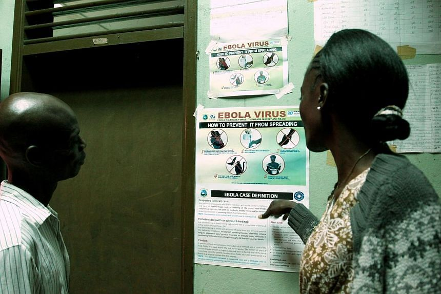Liberian people read an information sign about Ebola set on a wall of a public health center on July 31, 2014, in Monrovia.West Africa's Ebola-hit nations imposed stringent new rules to tackle the world's worst ever outbreak of the tropical vir