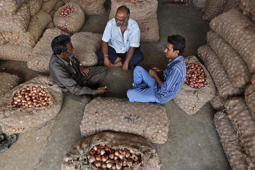 Traders sit amidst stacked sacks filled with onions and potatoes at a wholesale vegetable market in Ahmedabad. A World Trade Organisation pact to ease worldwide customs rules collapsed late on Thursday over India's demands for concessions on agricult