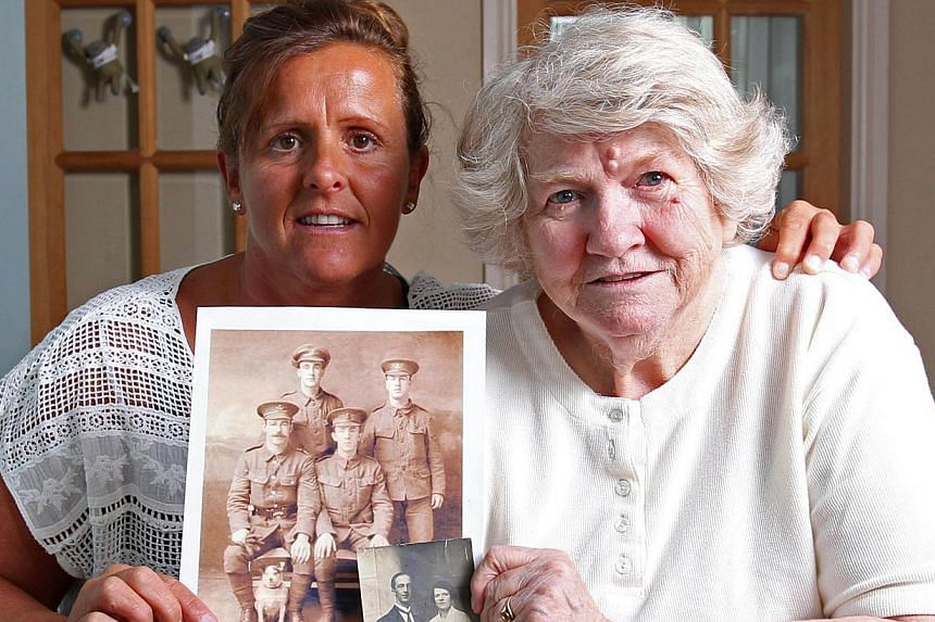 Amanda Nelson (left) and her mother Diane, granddaughter and daughter of former WWI British soldier Wilfred Smith, pose for pictures in Barnard Castle near County Durham, northern England, on July 11, 2014, as they look through pictures of Wilfred Sm