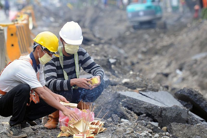 Rescue workers burn ghost money to the victims of the gas explosion in the southern Kaohsiung city on August 2, 2014. Shocked residents called on authorities on Saturday to relocate a number of industrial pipelines running underneath the country's de