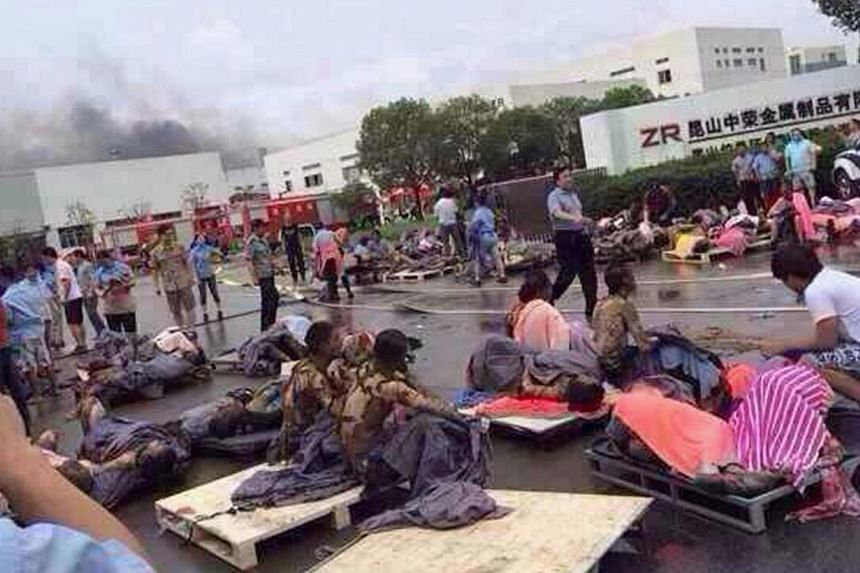 Rescuers help the victims of an explosion at the gate of a factory in Kunshan, Jiangsu province August 2, 2014. The blast killed 65 people, a government broadcaster said, while more than 100 were injured in what appeared to be an industrial accident.