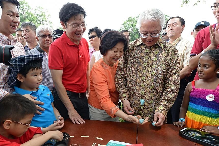 Minister for Culture, Community and Youth Lawrence Wong (in red) with President Tony Tan (second, right) and his wife (centre) at this year's Istana open house event on Saturday, Aug 2, 2014. -- ST PHOTO:NG SOR LUAN