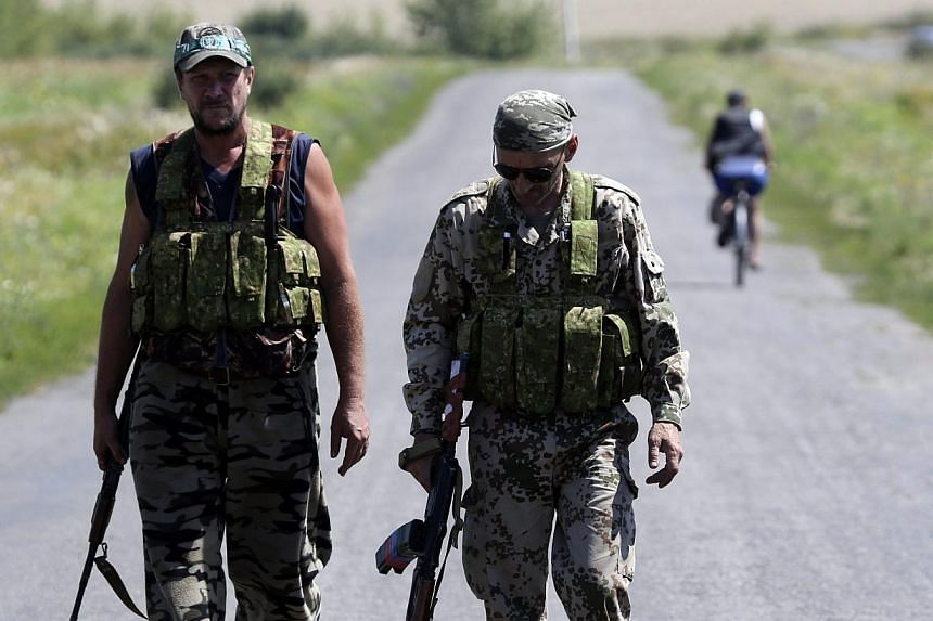 Armed pro-Russian separatists walk near the site where the downed Malaysia Airlines flight MH17 crashed, near the village of Hrabove (Grabovo) in Donetsk region, eastern Ukraine on Aug 1, 2014. Shelling close to the vast crash site of downed fli