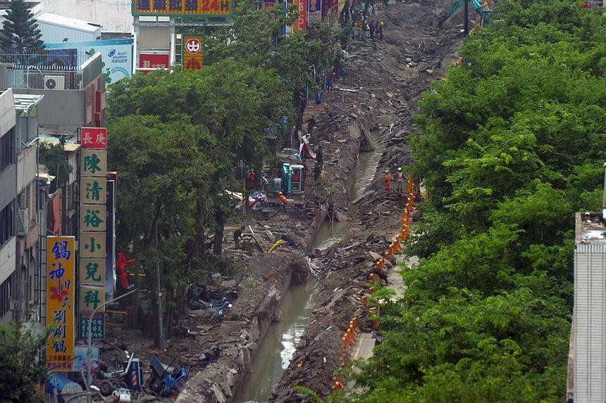 Soldiers and workers clean up a road ripped open by a gas explosion in Kaohsiung on Aug 2, 2014. -- PHOTO: AFP
