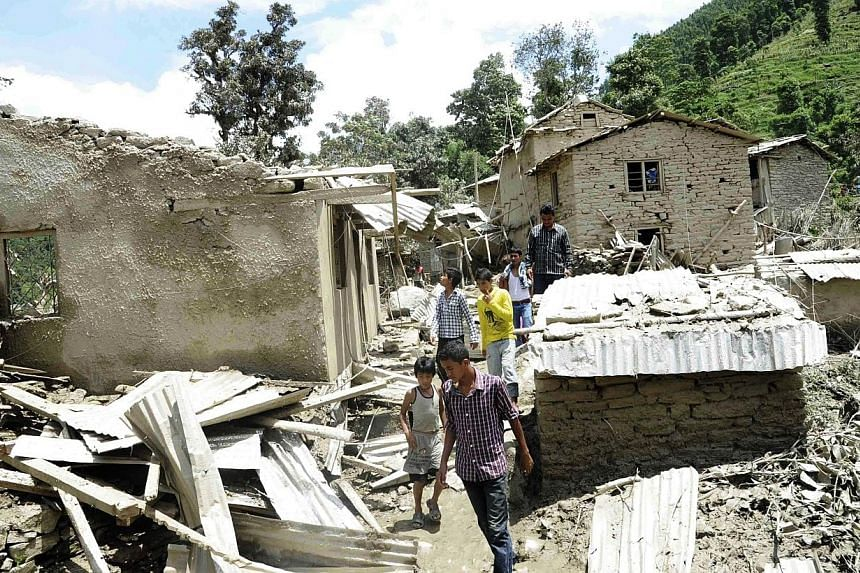 In this photograph released by the Nepalese Army on Aug 2, 2014, Nepalese residents stand near damaged houses after flooding near the scene of a landslide near the Sunkoshi River northeast of Kathmandu.Rescuers on Sunday, Aug 3, ruled out findi