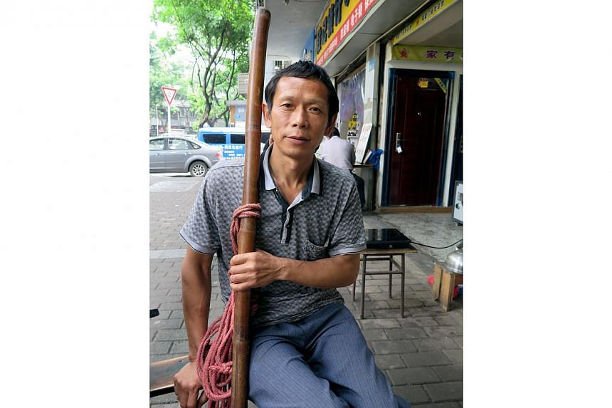 Deep lines edge the tanned face of Mr Shu Xiaoping, a hint of the life as a farmer he left behind when he moved from a rural village to the city centre of Chongqing more than a decade ago. A cigarette in hand and a sturdy bamboo pole in the other, th
