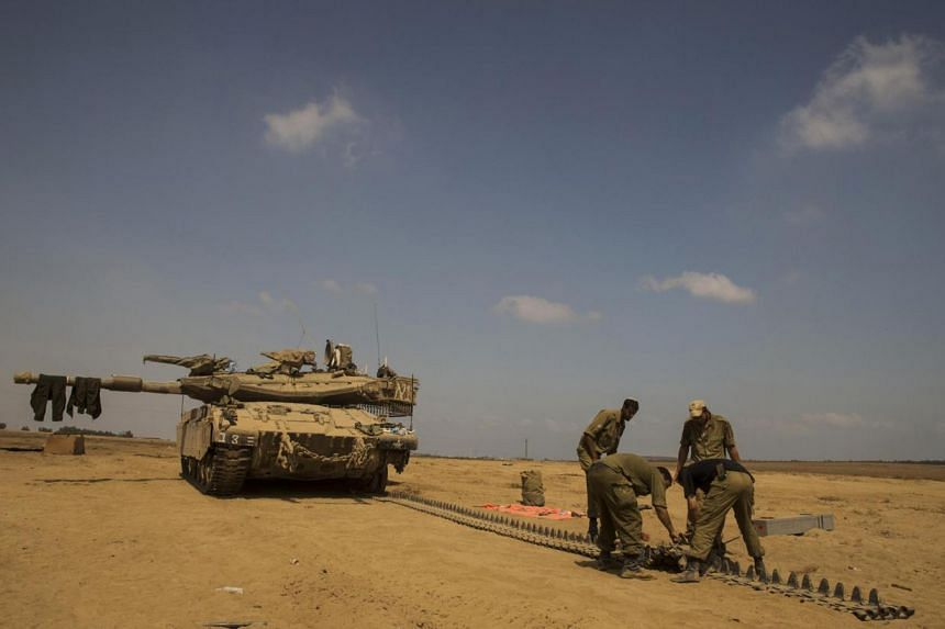 Israeli soldiers repair the track of a tank at a staging area outside the northern Gaza Strip July 29, 2014. Israel's military pounded targets in the Gaza Strip on Tuesday after Prime Minister Benjamin Netanyahu said his country should prepare for a
