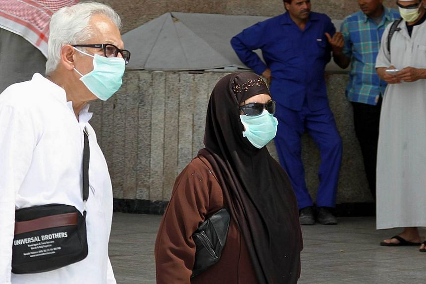 Muslim pilgrims wear nose and mouth masks on the way to Islam's holiest shrine, the Kaaba, in the Grand Mosque in the Muslim holy city of Mecca in Saudi Arabia on May 27, 2014. Saudi Arabia reported 10 confirmed new cases of a deadly respiratory