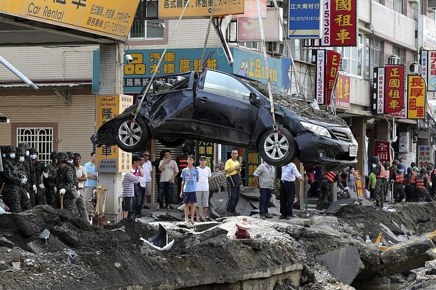 A damaged car is removed from the wreckage after an explosion in Kaohsiung, southern Taiwan, on Aug 2, 2014.The head of the company allegedly responsible for deadly explosions that rocked Taiwan's second city apologised on Sunday, Aug 3, as the
