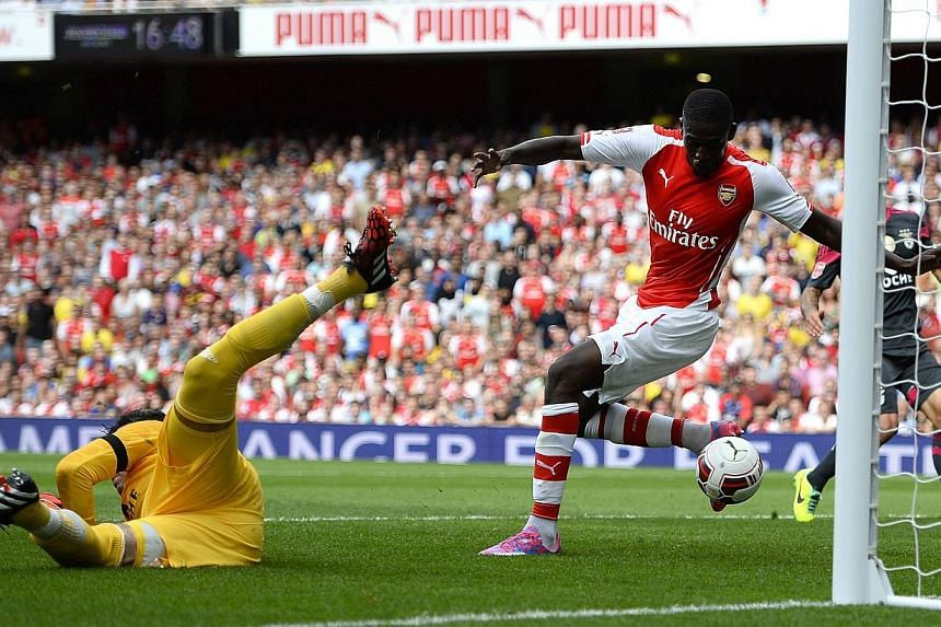 Arsenal's Yaya Sanogo (right) scores past Benfica's goalkeeper Moraes Artur during their Emirates Cup soccer match at the Emirates stadium in London on Aug 2, 2014. -- PHOTO: REUTERS