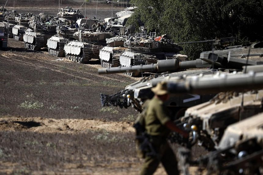 An Israeli soldier walks past Merkava tanks positioned on the Israeli side of the border with the Palestinian enclave as the sun sets on Aug 3, 2014. Palestinian groups, including representatives from Hamas and Islamic Jihad, held their first fo
