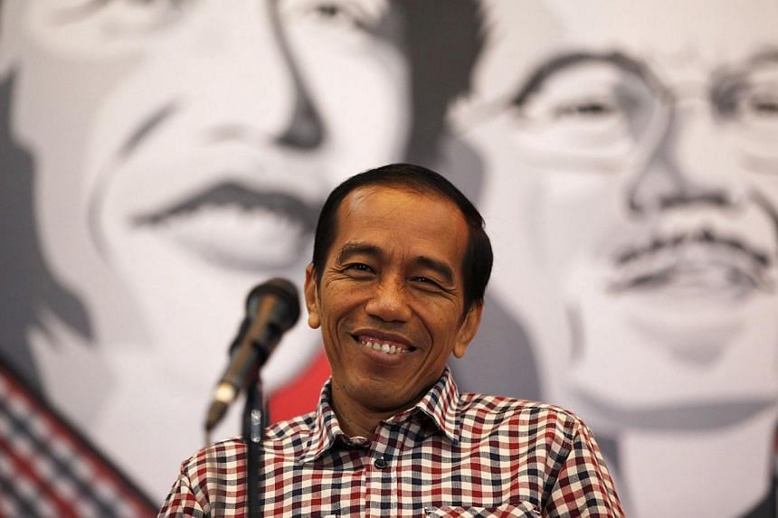 Presidential candidate Joko Widodo smiles during a news conference in Bandung July 3, 2014. Indonesia's president-elect Joko Widodo on Monday, Aug 4, 2014, announced a high-powered advisory team to handle his transition to power as he prepares t