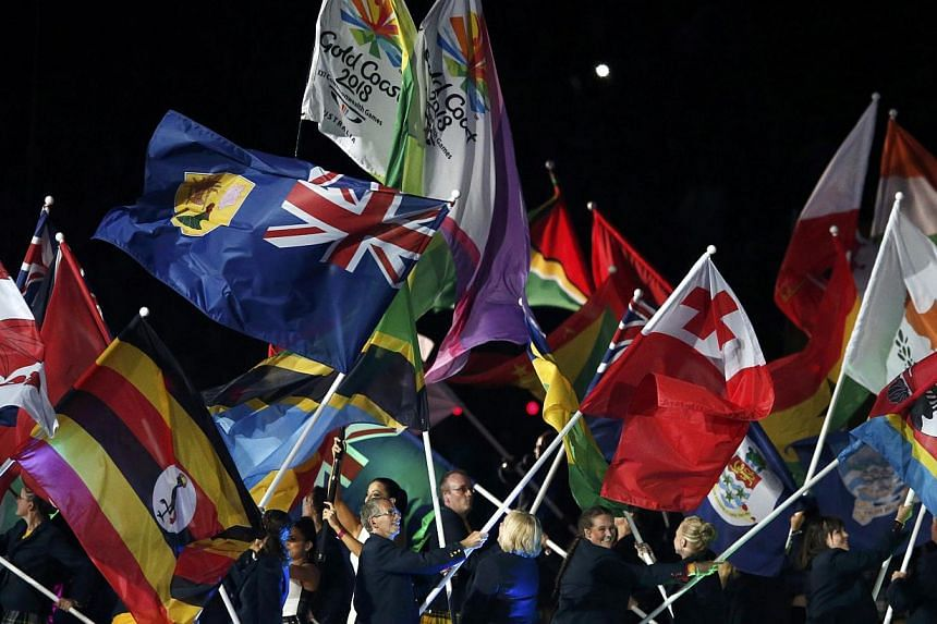 Performers wave flags during the closing ceremony of the 2014 Commonwealth Games at Hampden Park in Glasgow, Scotland on Aug 3, 2014. -- PHOTO: REUTERS