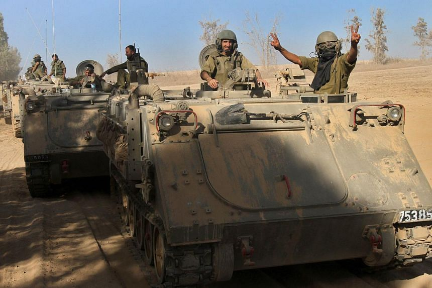 Israeli soldiers celebrate from their armoured personnel carriers (APC) along the border between Israel and the Gaza Strip after they pulled out from the Gaza Strip on Aug 3, 2014. -- PHOTO: AFP